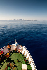 Sea trip to the volcanic island. Ship in the ocean. Turkey. View from the upper deck. People look away.