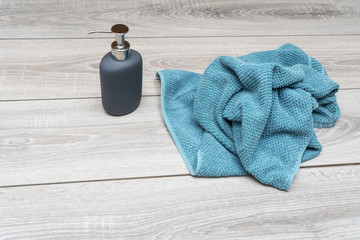 liquid soap dispenser and a towel on a wooden table