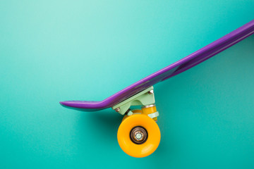 purple youth skateboard on turquoise background. children's plastic mini cruiser board. minimalism, flat lay, copy space