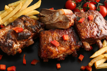 Delicious grilled ribs with french fries on plate, closeup