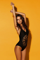 Young sexy slim tanned woman in black swimsuit posing against yellow background. Fashion portrait...