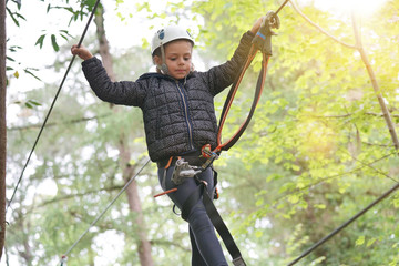 Little girl at adventure park climbing cables in trees