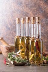 Bottles of olive oil with warious spices and herbs .