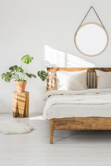 Monstera plant on a tree trunk night stand and a round mirror on a white wall in a sunlit bedroom interior with wooden furniture