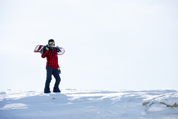 Image of man with snowboard on shoulders standing on snowy mountainside