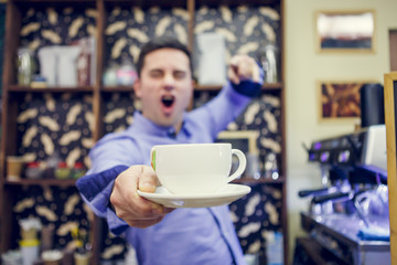 Image of barista man with cup in hands.