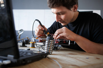 Picture of engineer with soldering iron repairing mechanism