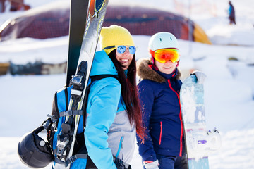 Image of two happy sports women with skis and sticks in winter