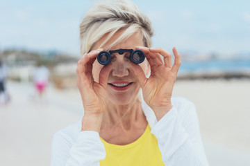 Woman looking at the camera through binoculars