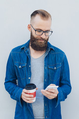 Man holding takeaway coffee texting on his mobile