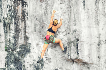 Young blonde woman climbing a cliff without insurance