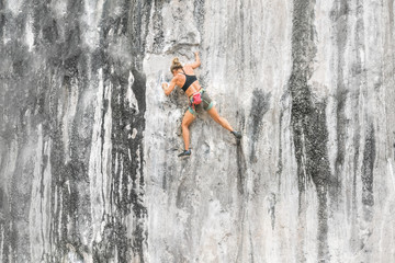 Young woman climbing up a cliff without insurance. Adrenaline, strenght, ambition