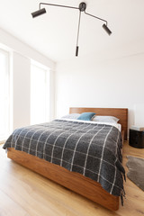 Lamp above wooden bed with patterned blanket in simple white bedroom interior. Real photo