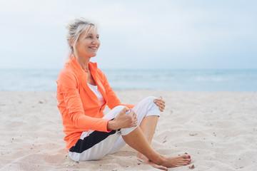 Happy supple mature blond woman on a beach