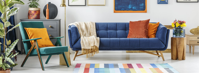 Real photo of a teal green armchair standing next to a blue couch i living room interior with flowers on a wooden stool and painting on the wall