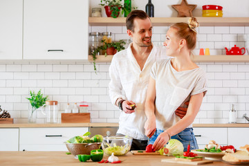 Picture of beautiful loving couple cooking vegetables in kitchen at apartment