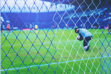 Goalkeeper and players during worm up practice before a soccer match. select focus at the net