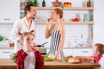 Photo of young parents with son and daughter preparing breakfast