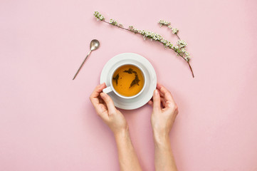 A cup of tea in the hands of a young woman with a branch of spring flowers on a pastel pink background top view with copy space. Flat lay Spring background.