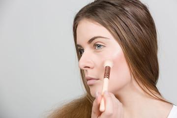Teenager trägt Rouge Make Up auf
