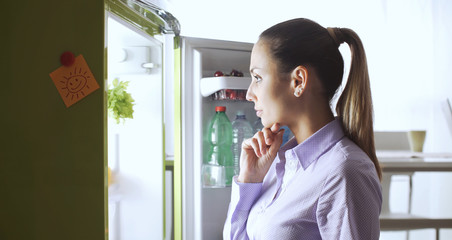 Young woman looking into the fridge