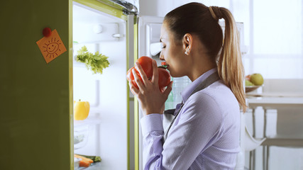Woman taking healthy vegetables from the fridge