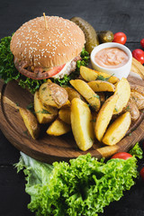 Tasty burger with fried potatoes on wooden board