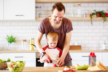 Image of man with son cooking vegetables