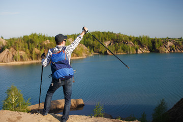 Image from back of young tourist with backpack with arms raised with walking sticks on background of mountain landscape