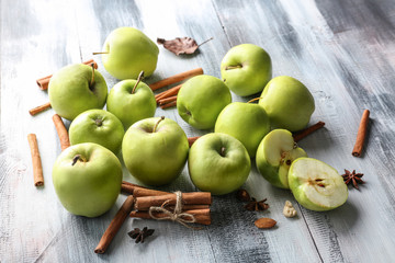Fresh apples and cinnamon sticks on wooden background