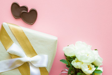 Gift box with white ribbon, bouquet of fresh roses and chocolate hearts on pastel pink desk. Lovely, romantic surprise for beloved. Empty place for inspirational, emotional, sentimental text or quote.
