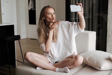 Cheerful young woman dressed in white shirt taking selfie