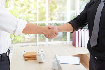 Business handshake. Business associate shaking hands in office.