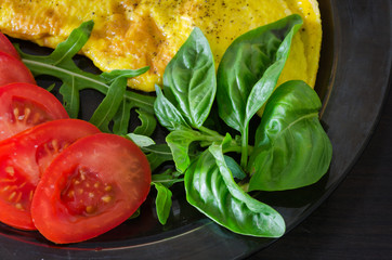 Omelette on a plate with rucola, basil and tomato