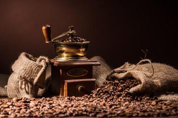 vintage coffee grinder with sacks of coffee on dark brown background