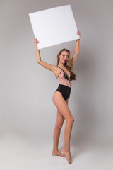 Be glamorous and sexual! Full length portrait of the pretty young well-graced female holding the empty board over her head in the studio.