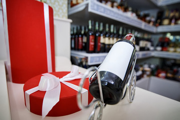A red gift box with a white bow and a bottle of wine with a white label on a stand against the backdrop of a showcase with alcohol.