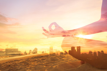 Feeling at peace in the city and meditation concept. double exposure of hand meditating on the beach against city background.  Wall mural