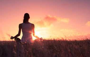 Peaceful quiet meditation. Woman meditating in a grass meadow.