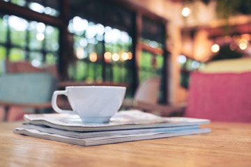 Closeup image of a white cup of hot coffee above the books on wooden table with blur background in cafe