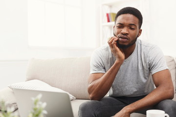 Young african-american man having toothache at home