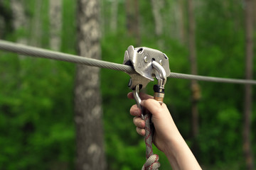 Hands holding carabiner on zip line