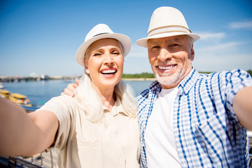 Portrait of stylish trendy senior couple in casual outfits straw hats shooting selfie on front camera over blurred river background having good mood enjoying sunny day sunshine