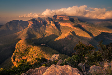A wide shot of the Three Rondavels and surrounding landscape lit up with dramatic texture and form at sunset golden hour. Mpumalanga, South Africa