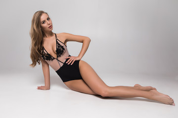 Lingerie is my next love after clothing! Beautiful sexy young girl in bikini lying on the floor of the professional photo studio.