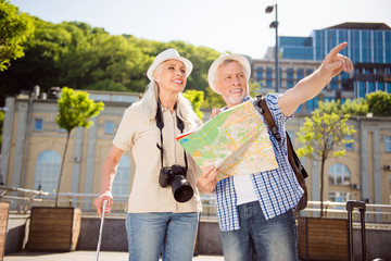 Portrait of two active stylish traveler with bags photo camera in straw hats casual outfits holding map in hands, handsome man gesturing right route with index finger. Destination concept
