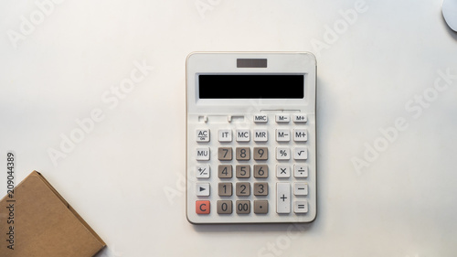 Wall mural Office desk table with calculator Top view with notebook on white background