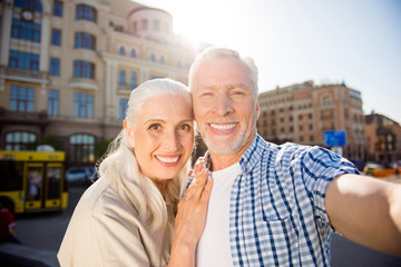 Self portrait of cheerful positive grandma and granddad shooting selfie on front camera over blurred buildings having video-call