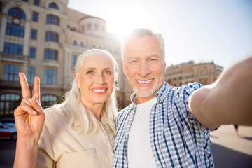 Hi! Rest relax leisure concept. Self portrait of friendly peaceful grandma and granddad shooting selfie on front camera over blurred buildings having video-call gesturing v-sign with two fingers