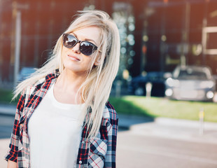 Beautiful blond young woman walking on the city street.